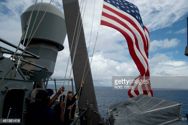 US Navy personnel raise their flag during the bilateral maritime exercise between the Philippine Navy and US Navy dubbed Cooperation Afloat Readiness...