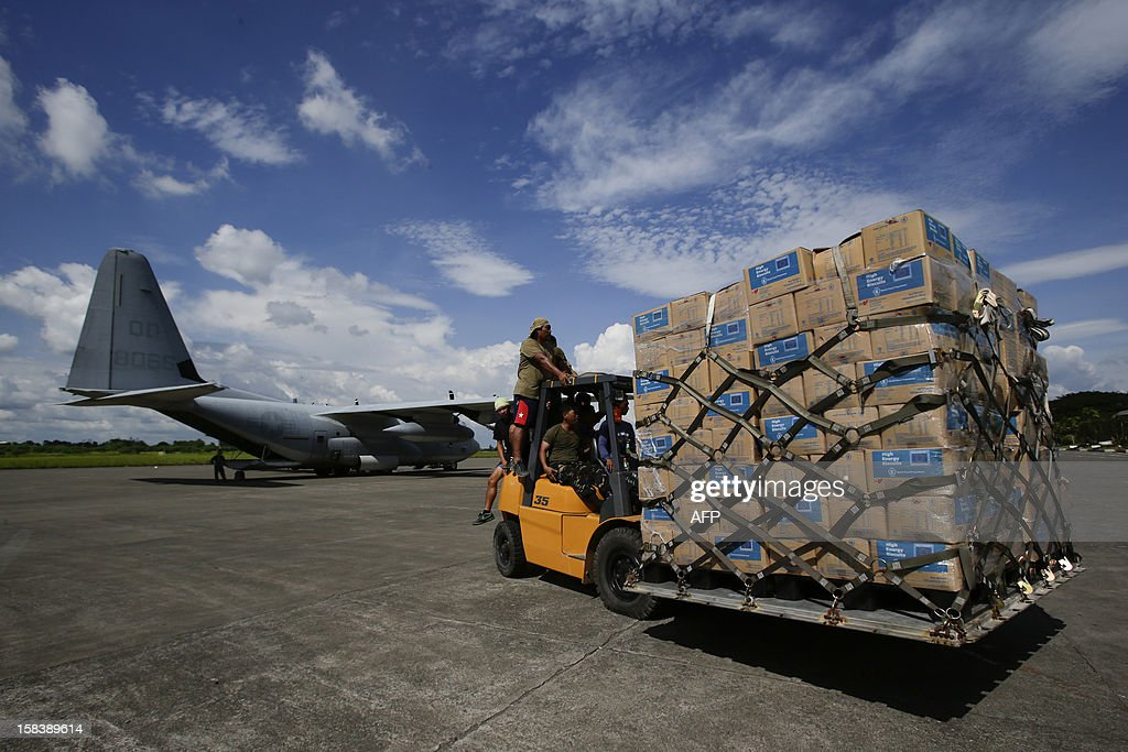 US Navy personnel unload relief goods to be transported to regions affected by Typhoon Bopha aboard the Marine Corps KC-130J Hercules millitary aircraft inside the International Airport in Davao, Mindanao on December 15, 2012. US Marines, the Philippine Armed forces and various non-profit organisations have been working together to provide humanitarian assistance and disaster relief support at the request of the Philippines government in the wake of Typhoon Bopha, which made landfall on December 4, 2012. The death toll from the strongest typhoon to hit the Philippines this year has climbed above 900, with hundreds still missing, the government said on December 13. AFP PHOTO / POOL / John Javellana