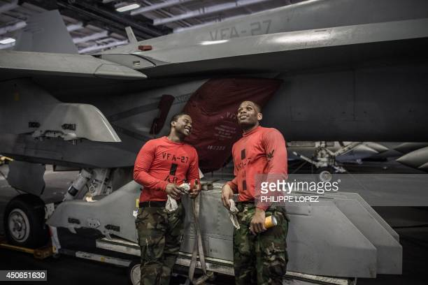 Navy 'red shirt' personnel share a light moment beside a Boeing F/A18 Super Hornet multirole fighter aircraft in the hangar of the US nuclearpowered...