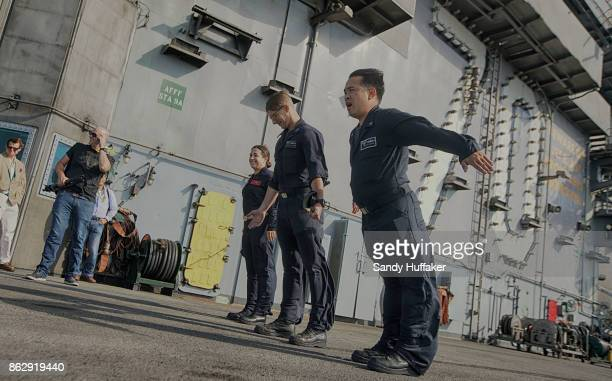 Navy Sailor TomTonthat leans into the wind with other sailors on the flight deck during training exercises aboard the USS Carl Vinson on October 18...