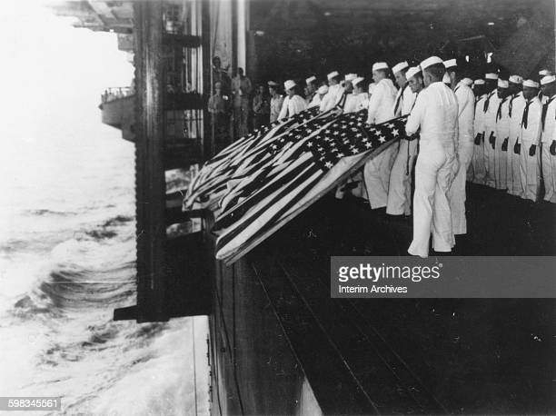 US Navy sailors gather to honor shipmates killed in action during a burial at sea on board the USS Intrepid off Luzon World War II 1940s