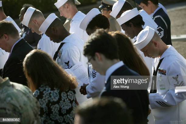 Navy sailors participate in an observance to commemorate the anniversary of the 9/11 terror attacks at the Pentagon Memorial September 11 2017 in...