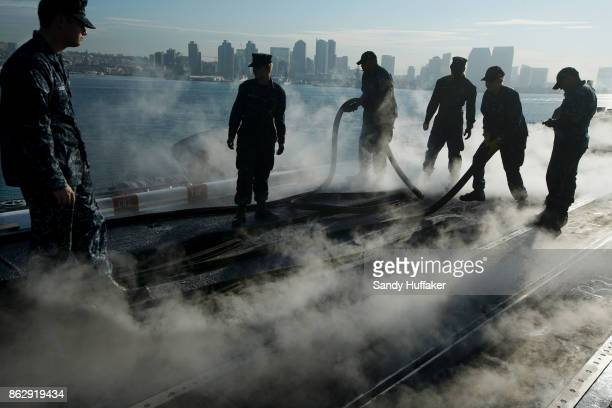 Navy Sailors prepare the flight deck during training exercises aboard the USS Carl Vinson on October 18 2017 in San Diego California The Navy will...
