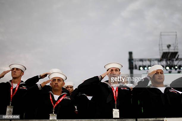 Navy Sailors salute before the start of University of North Carolina v Michigan State game aboard the Aircraft Carrier USS Vinson during the Carrier...