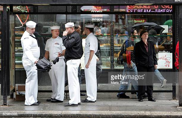 S Navy sailors wait at a bus stop in Times Square during Fleet Week May 26 2005 in New York City Fleet Week honors US armed forces and runs through...