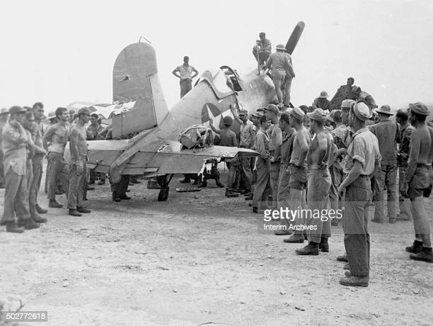 US Navy Seabees and Marines pose beside Vought F4U Corsair with a heavily damaged tail Bougainville Island Papua New Guinea 1944