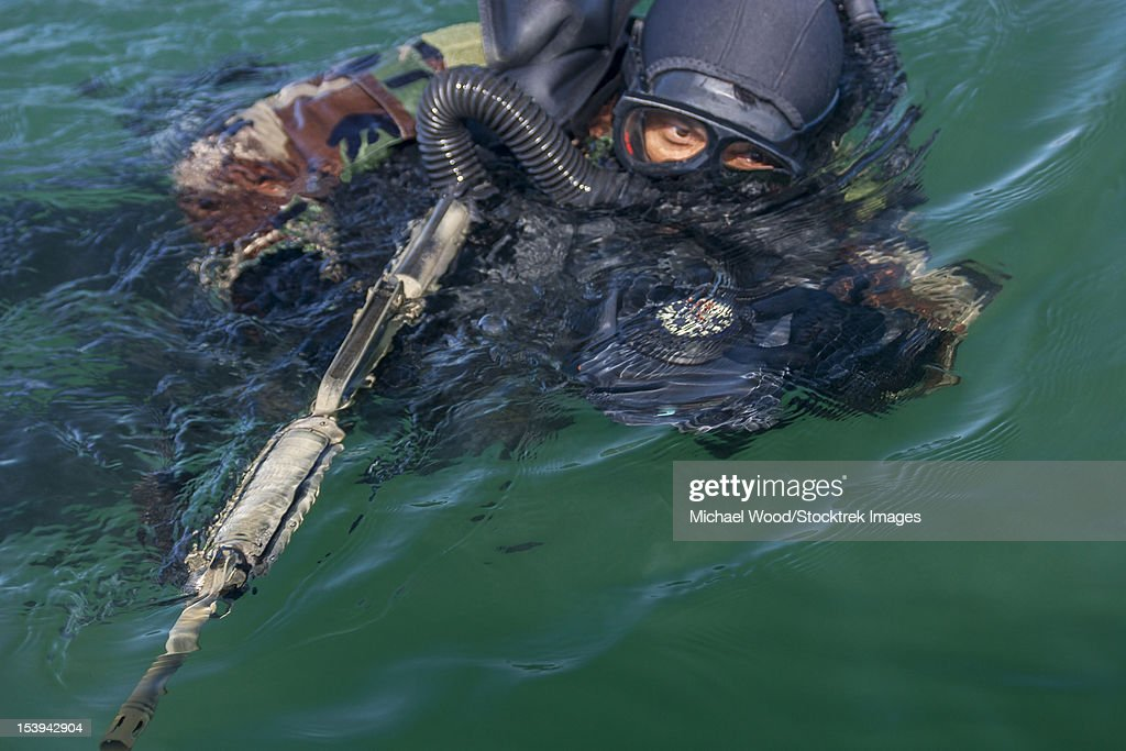 A Navy SEAL combat swimmer, wearing an oxygen rebreather called FROGS, swims sidestroke carrying a navigation board and a M4 carbine on a training dive.