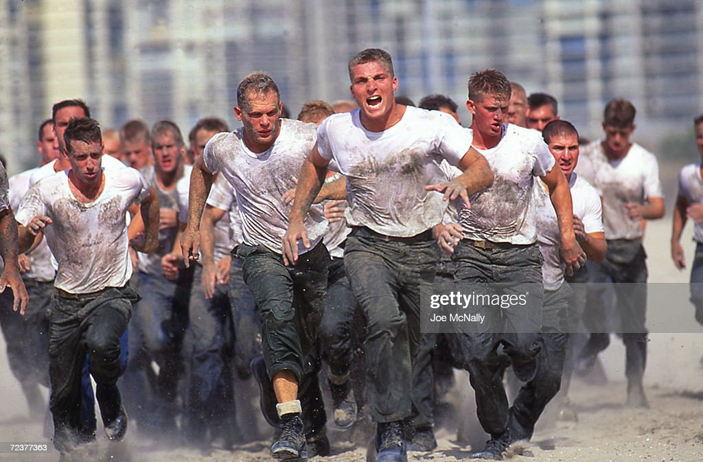 Navy Seal trainees rush the beach under orders in this undated photo taken in 2000 at the Coronado Naval Amphibious Base in San Diego, California. Hell Week at this beach in San Diego is exactly what it sounds like for third-week Navy trainees who are subjected to nearly unimaginable physical and mental trials. Only the strongest survive the nonstop physical exercise of jogging for miles in deep sand, carrying heavy rubber boats back and forth through the surf, crawling through mud under simulated machine gun fire, and doing myriads of pushups on demand. Hunger, thirst and hallucinations are among the symptoms the men experience, often after only two days. The recruits are divided into teams, and if a team fails to complete a task in the allotted time, all its members must carry 'Old Misery,' a 350-pound log.  Fewer than half the men survive the week to become Seals, an elite maritime commando force.  (Photo by Joe McNally/Getty Images)