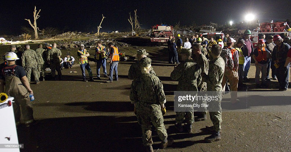 Navy see-bees civic employees and firefighters regroup their efforts as emergency crews continued searching for victims in the early morning hours on Tuesday, May 21, 2013, in Moore, Oklahoma, after a tornado ripped through part of the town.