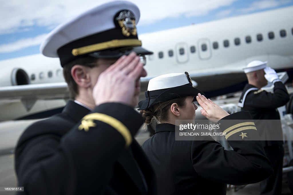 US Navy service members salute outside Delta Flight 1172 during a dignified transfer at Dulles International Airport March 7, 2013 in Sterling, Virginia. The remains of two unknown soldiers from the US Civil War (1861-1865) found inside the sunken iron clad ship, the USS Monitor, were transfered for burial at Arlington National Cemetery after being discovered in 2002 and being sent to Joint POW/MIA Accounting Command in Hawaii for possible genetic identification. AFP PHOTO/Brendan SMIALOWSKI