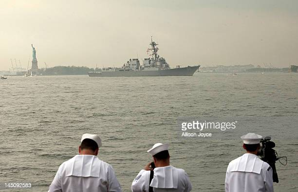 Navy service members watch as the USS Roosevelt passes the Statue of Liberty on the Hudson River during the Parade of Ships for the start of Fleet...