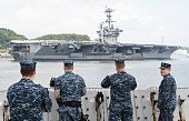US Navy servicemen see off the nuclearpowered aircraft carrier USS George Washington as it leaves the US naval base in Yokosuka 60 kms south of Tokyo...