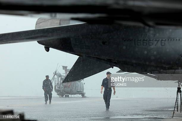 US Navy servicemen walk on the flight deck of the USS Carl Vinson aircraft carrier during a heavy rainstorm in Hong Kong on May 22 2011 The US Navy...