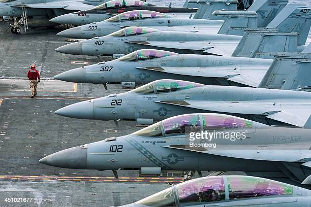 A US Navy technician walks past a row of F/A18 Super Hornet combat jets manufactured by Boeing Co aboard the USS George Washington aircraft carrier...