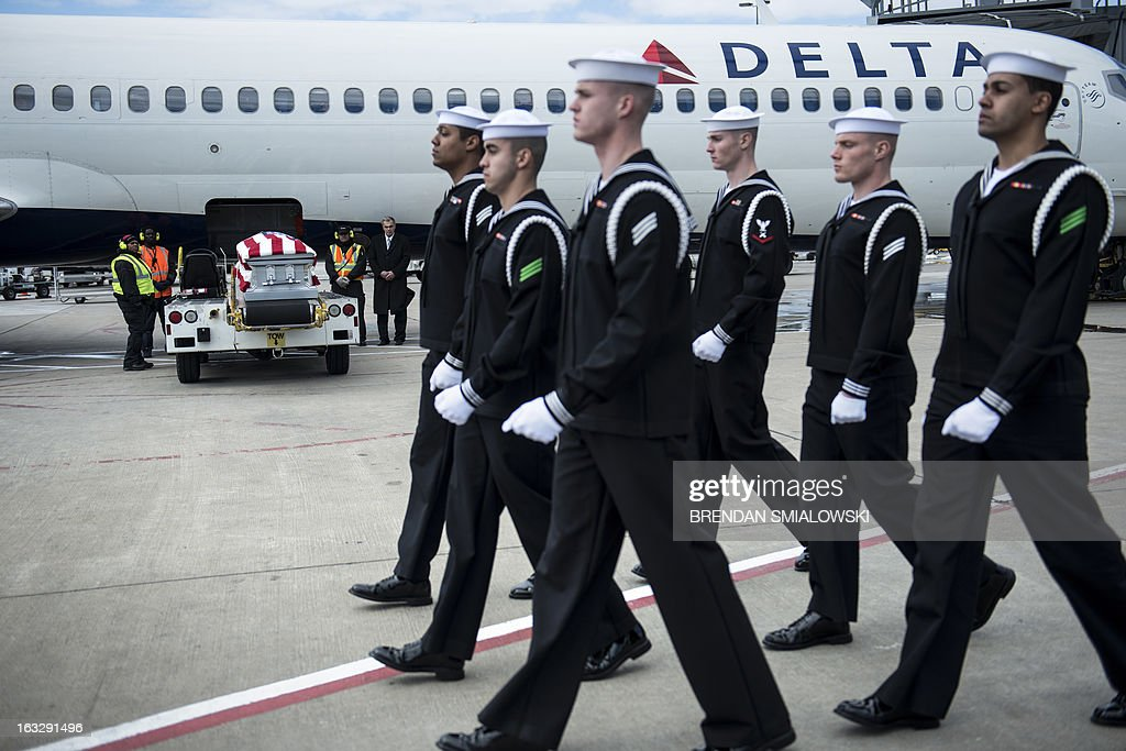 Navy transfer team walks toward Delta Flight 1172 during a dignified transfer at Dulles International Airport March 7, 2013 in Sterling, Virginia. The remains of two unknown soldiers found inside the sunken iron clad ship, the USS Monitor, were transfered for burial at Arlington National Cemetery after being discovered in 2002 and being sent to Joint POW/MIA Accounting Command in Hawaii for possible genetic identification. AFP PHOTO/Brendan SMIALOWSKI