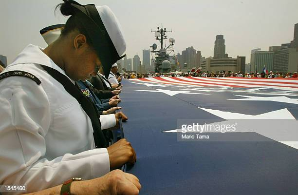 S Navy YNSN Raquita Walker bows her head during the closing prayer as she holds a giant American flag that flew over Ground Zero during Memorial Day...