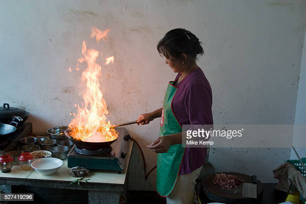 Naxi minority husband and wife cook pork and vegetable dishes at a small roadside restaurant near to Zhongdian in Yunnan province The man thinly...