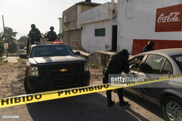 A Nayarit police officer gathers a driver's information at a check point near the blocked off area where forces killed Juan Francisco Patrón Sánchez...