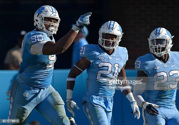 Nazair Jones Myles Dorn and Cayson Collins of the North Carolina Tar Heels celebreate after a fourth down stop against the Georgia Tech Yellow...