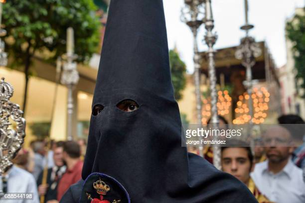 Nazarene penitent with the typical conical hood walking in front of a procession During the Easter week processions with the image of Christ and the...