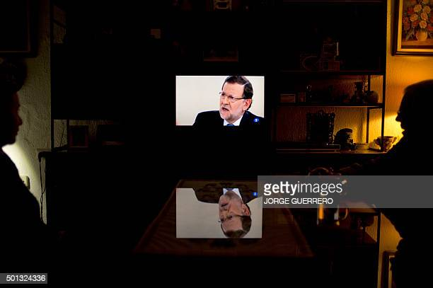 Nazario and his daughter Milagros watch a TV debate between Spanish Prime Minister and Popular Party leader Mariano Rajoy and leader of Spanish...