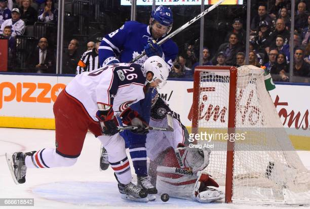 Nazem Kadri of the Toronto Maple Leafs and Kyle Quincey of the Columbus Blue Jackets look for the puck after a save by Joonas Korpisalo of the...