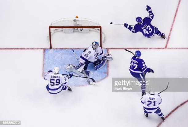 Nazem Kadri of the Toronto Maple Leafs celebrates his goal with teammate Leo Komarov against Andrei Vasilevskiy Brayden Point and Jake Dotchin during...