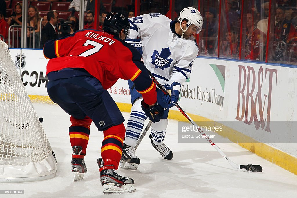 Nazem Kadri #43 of the Toronto Maple Leafs digs the puck out from the boards against Dmitry Kulikov #7 of the Florida Panthers at the BB&T Center on February 18, 2013 in Sunrise, Florida.