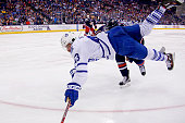 Nazem Kadri of the Toronto Maple Leafs is tripped by Nick Foligno of the Columbus Blue Jackets while chasing after the puck during the third period...
