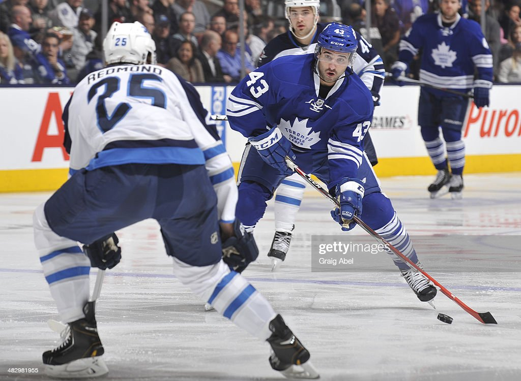 <a gi-track='captionPersonalityLinkClicked' href=/galleries/search?phrase=Nazem+Kadri&family=editorial&specificpeople=4043234 ng-click='$event.stopPropagation()'>Nazem Kadri</a> #43 of the Toronto Maple Leafs looks to shoot the puck as <a gi-track='captionPersonalityLinkClicked' href=/galleries/search?phrase=Zach+Redmond&family=editorial&specificpeople=8234699 ng-click='$event.stopPropagation()'>Zach Redmond</a> #25 of the Winnipeg Jets defends during NHL game action April 5, 2014 at the Air Canada Centre in Toronto, Ontario, Canada.