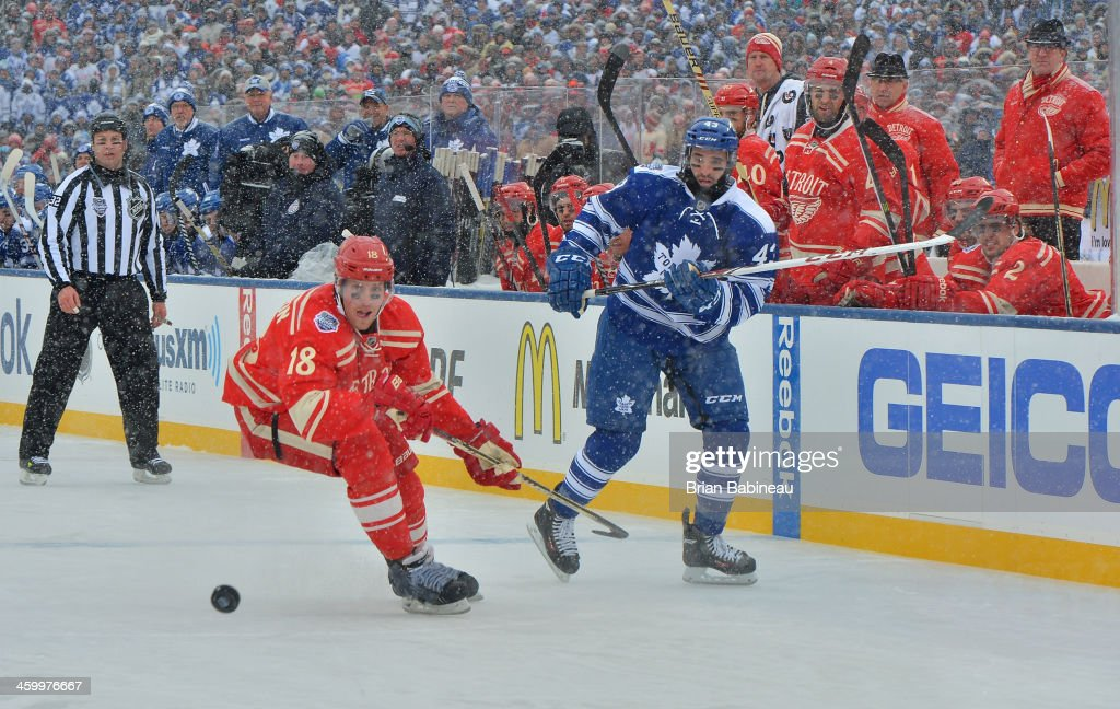 <a gi-track='captionPersonalityLinkClicked' href=/galleries/search?phrase=Nazem+Kadri&family=editorial&specificpeople=4043234 ng-click='$event.stopPropagation()'>Nazem Kadri</a> #43 of the Toronto Maple Leafs shoots the puck past Joakim Andersson #18 of the Detroit Red Wings into the Wings zone in the first period during the 2014 Bridgestone NHL Winter Classic on January 1, 2014 at Michigan Stadium in Ann Arbor, Michigan.