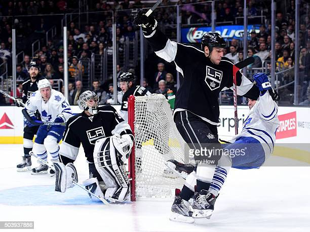 Nazem Kadri of the Toronto Maple Leafs takes a check from Milan Lucic of the Los Angeles Kings in front of Jonathan Quick during the first period at...