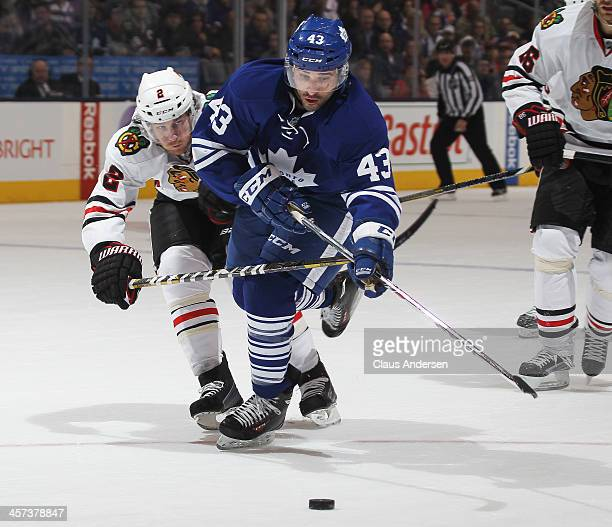 Nazem Kadri of the Toronto Maple Leafs tries to get a shot away while being checked by Duncan Keith of the Chicago Blackhawks during an NHL game at...