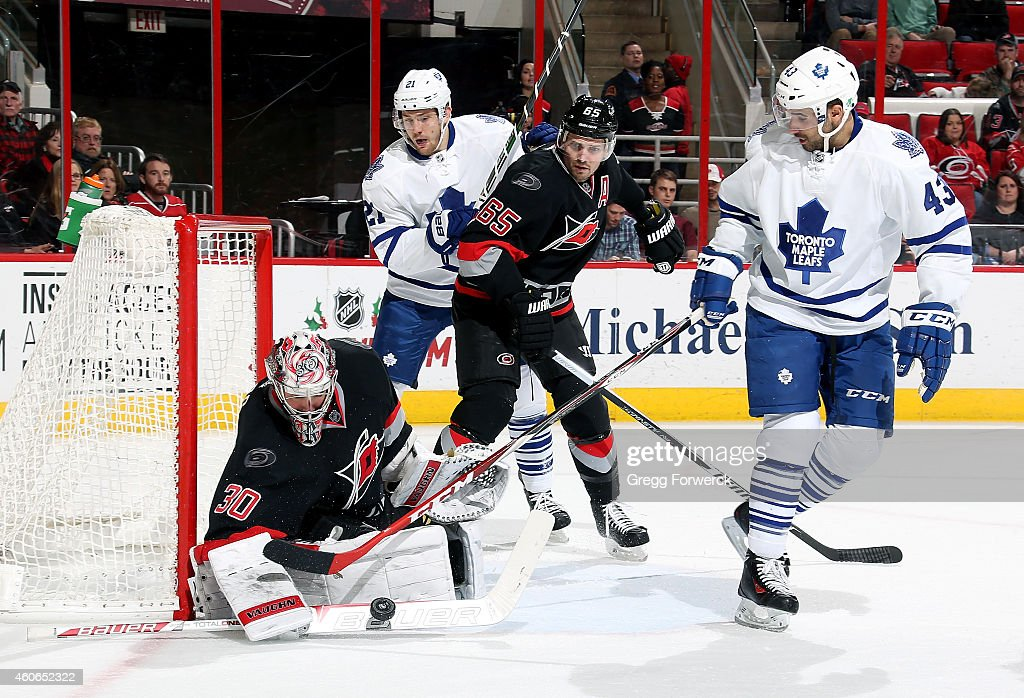 <a gi-track='captionPersonalityLinkClicked' href=/galleries/search?phrase=Nazem+Kadri&family=editorial&specificpeople=4043234 ng-click='$event.stopPropagation()'>Nazem Kadri</a> #43 of the Toronto Maple Leafs tries to get his stick to a loose puck guarded by <a gi-track='captionPersonalityLinkClicked' href=/galleries/search?phrase=Cam+Ward&family=editorial&specificpeople=453216 ng-click='$event.stopPropagation()'>Cam Ward</a> #30 of the Carolina Hurricanes as James van Riemsdyk #21 and <a gi-track='captionPersonalityLinkClicked' href=/galleries/search?phrase=Ron+Hainsey&family=editorial&specificpeople=206345 ng-click='$event.stopPropagation()'>Ron Hainsey</a> #65 look on during their NHL game at PNC Arena on December 18, 2014 in Raleigh, North Carolina.