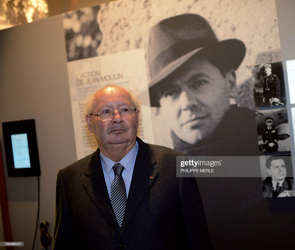 Nazi hunter, French lawyer and President of the 'Association des fils et filles des deportes juifs de France' (Sons and daughters of Jews deported from France), Serge Klarsfeld poses during an exhibition dedicated to French Resistance leader during World War II, Jean Moulin (seen on a poster), on November 14, 2012 at the Centre of History of French Resistance and Deportation (CHRD) in Lyon, eastern France, two days ahead of its reopening after a one-year revamp. AFP PHOTO PHILIPPE MERLE