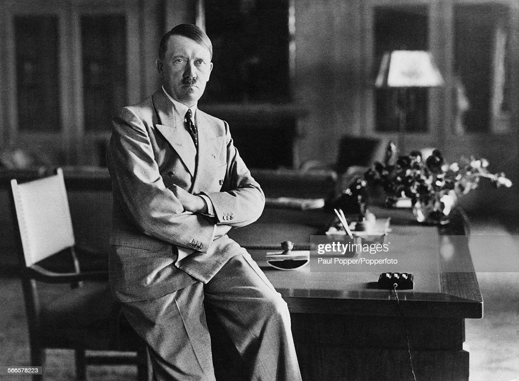 Nazi leader Adolf Hitler (1889 - 1945), sitting on the edge of a desk at his Berghof residence, Berchtesgaden, Bavaria, Germany, circa 1940.