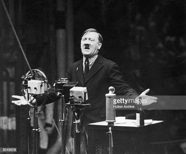 Nazi leader Adolf Hitler speaks in front of microphones and gestures with his hands Original Publication From the newsreel 'The March of Time'