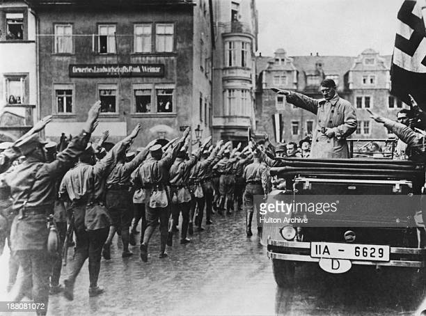 Nazi leader Adolf Hitler takes the salute as Sturmabteilung paramilitaries march past in the market square in Weimar Germany 13th November 1930 On...