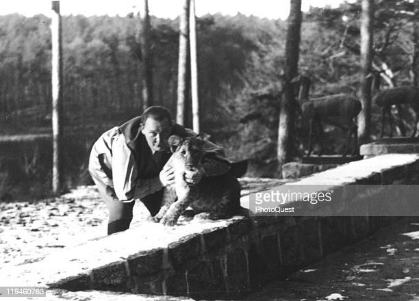 Nazi leader Hermann Goering poses with his pet lion Mucki on the grounds of his villa Carinhall Prussia April 5 1936