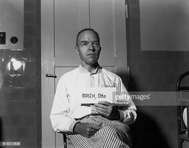 Nazi Otto Rasch Brigadier General in the SS member of the SD and member of the Gestapo holds his name up on a card He is on trial in Nurnburg
