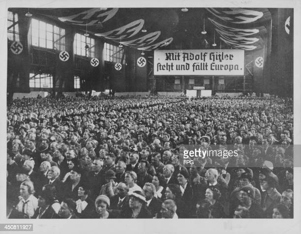 A Nazi Party rally with the sign 'Europe Stands and Falls with Adolf Hitler' prior to World War Two Germany circa 19301940