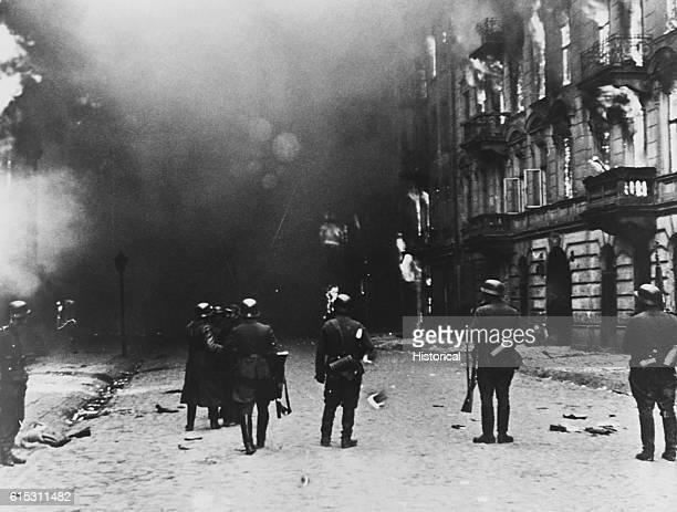 Nazi soldiers watch their handiwork as the Warsaw ghetto burns