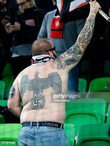 Nazisymbol tattooed ultra fan of Budapest Honved holds a flag during the Hungarian OTP Bank Liga match between Ferencvarosi TC and Budapest Honved at...