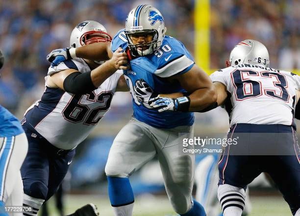 Ndamukong Suh of the Detroit Lions tries to get through the blocks of Ryan Wendell and Dan Connolly of the New England Patriots during the first...