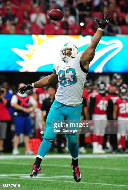 Ndamukong Suh of the Miami Dolphins attempts to bat away a pass against the Atlanta Falcons at MercedesBenz Stadium on October 15 2017 in Atlanta...