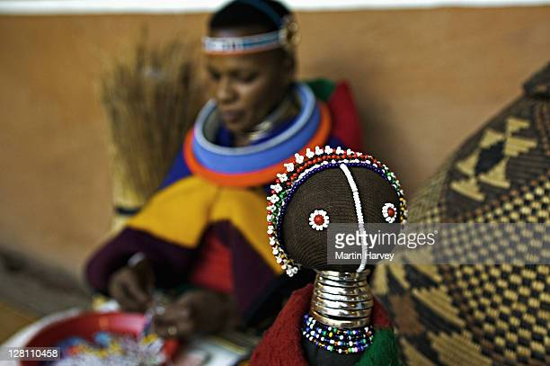 Ndebele women make colorful dolls in the style of traditional Ndebele costumes. Lesedi Cultural Village near Johannesburg, South Africa
