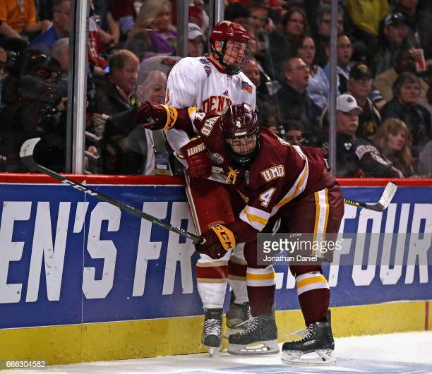 Neal Pionk of the MinnesotaDuluth Bulldogs checks Tariq Hammond of the Denver Pioneers into the boards during the 2017 NCAA Division I Men's Ice...