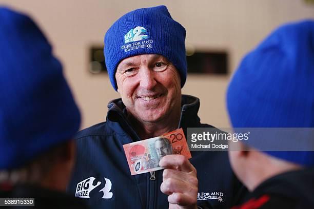 Neale Daniher accepts a donation from Kevin Sheedy during an Essendon Bombers AFL media and training session at True Value Solar Centre on June 9...