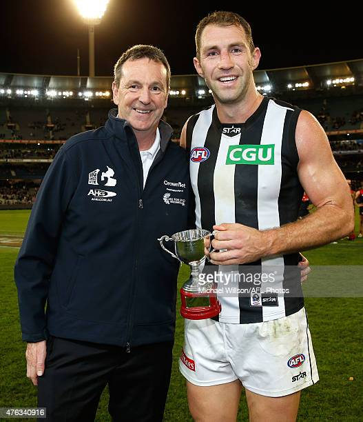 Neale Daniher presents the inaugural 'Neale Daniher Trophy' to Travis Cloke of the Magpies during the 2015 AFL round ten match between the Melbourne...