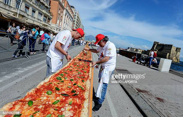 TOPSHOT Neapolitan pizza makers attempt to make the longest pizza to break a Guinness World Record along the seafront of Naples on May 18 2016 For...
